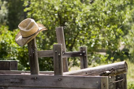 old wood farm wagon: A straw cowboy hat hanging from a post on an old wood wagon. Stock Photo
