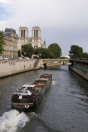 downstream: A French river boat moving downstream on the Seine River in the narrow river channel near Notre Dame and the Ile de France.