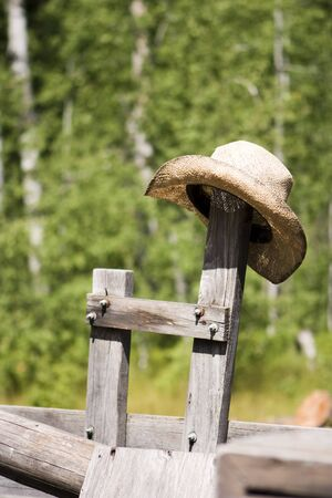 A straw cowboy hat resting on an old wooden post on an old kitchen wagon.