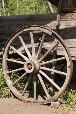 old wood farm wagon: An old, weathered wagon wheel in the American West is an example of the rustic charm of the country. This wheel is covered with an iron strip for durability.