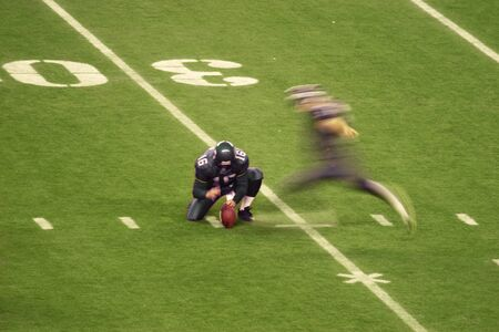 An American high school football kicker attempting a field goal from the thirty yard line. The motion blur of the kicker shows the movement while the holder is almost stationary. Imagens
