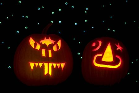 Two carved pumpkins, lighted with candles, are placed in front of a backdrop of hundreds of googly eyes that are lit up with ultraviolet light. One pumpkin is carved as a snake and the other with a sorcerers hat. photo