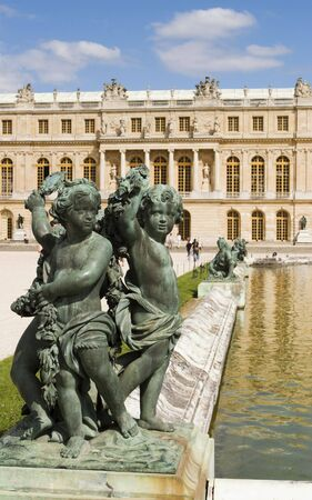cherubs: Three ornamental cherubs are at one of the corners of a pond in the Versailles gardens.  Stock Photo