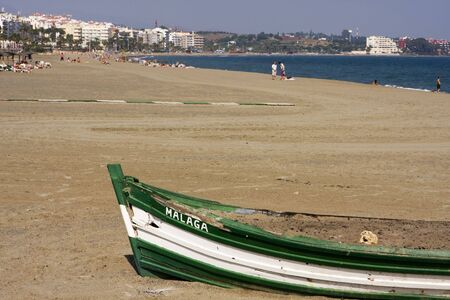 sol: Boat on Costa del Sol. An old boat, filled with sand, is used as a barbecue pit on the beach at Estepona on Spains Costa del Sol.