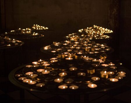 flickering: Prayer Candles. Hundreds of little tea light candles are lit at Notre Dame cathedral in Paris to give emphasis to peoples prayers. The candles were flickering through the exposure which results in a soft image.