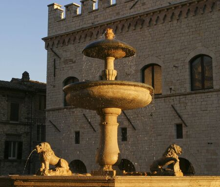 italian fountain: An old Italian fountain in the main town square of Assissi. Droplets of water from the fountain are highlighted in the warm golden glow of the evening just before sunset. Stock Photo