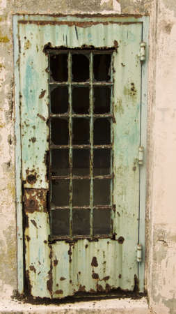 neglect: A rusty door at the old Alcatraz maximum security prison in San Francisco. This door, once painted green, has rusted out over the years due to a lack of maintenance and is now a symbol of neglect.