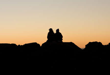 A couple, sitting on a pile of rocks at the beach, are watching a colorful sunset. photo