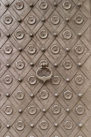 centered: The main door to Karlstein Castle in the Czech Republic is covered with ornate iron decorations in a traditional and functional style with crossing iron straps providing additional strength. The door kncoker is centered in the middle of the door.