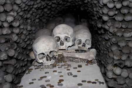 At the Sedlice All Saints bone church in Kutna Hora, a display of skulls is surrounded by donations of various coins. The walls surrounding the skulls are made of various bones from legs and arms. A scary image for Halloween. Stock fotó