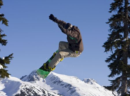 A snowboarder at Whistler catching some big air. With this angle, he appears to be jumping over Blackcomb Mountain. photo