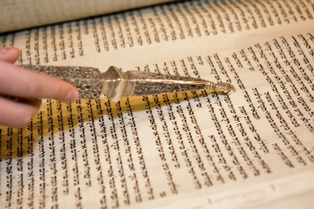 bar mitzvah: An old Torah scroll being read at a bar mitzvah with a hand holding a traditional yad.