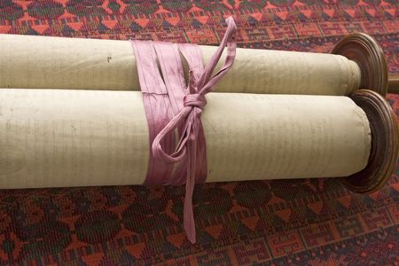 scroll: A 150 year-old vintage torah scroll tied with a faded purple ribbon to keep it from unrolling.