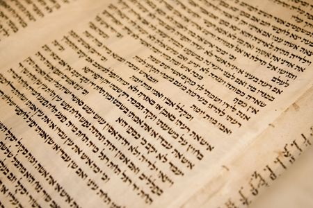 Hebrew text on one panel of a antique Torah scroll that is 150 years old. The traditional stitching holding the parchment panels together is visible. photo