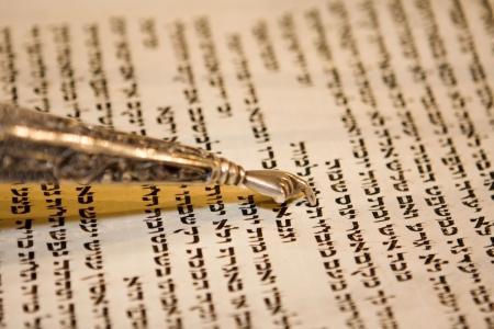 棒 mitzvah 式の間に、羊皮紙にテキストに向かって指している伝統的なヤド Torah スクロールを読んでください。