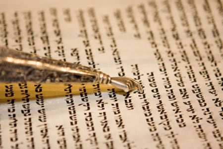 mitzvah: Reading a Torah scroll during a bar mitzvah ceremony with a traditional yad pointing towards the text on the parchment.