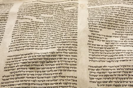 scripture: A part of the Hebrew text from a portion of a Torah scroll. This scroll is estimated to be 150 years old and is wrinkled and spotted with age. Stock Photo