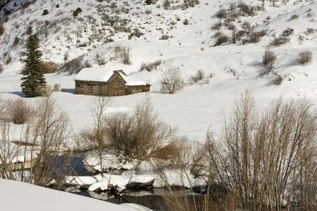 A small barn in a rural area near Aspen, Colorado is completely covered with snow. In the foreground, a small stream is running. photo