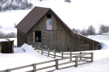 An old barn with a split-rail wood fence meandering to it. The weathered old wood is grayish with age but has successfully withstoood considerable time. photo