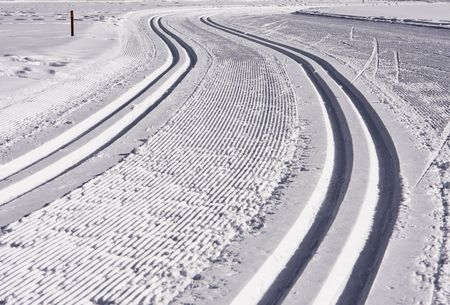 disappears: A cross-country ski track in Aspen forms an S-shaped trail that disappears into the distance. The parallel lines of the groomed path and the more deeply indented ski tracks give this image some shape. Stock Photo
