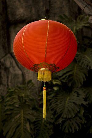 papierlaterne: Eine rote Laterne Papier mit gelben Quasten hell leuchtendes gegen einen dunklen Hintergrund der Pflanzen und einen gro�en Stein.