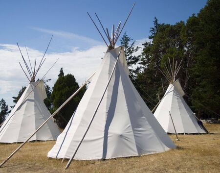tipi: Three teepees together in a camp. This is a traditional form of shelter for native Americans, particularly for the Great Plains and American West. Stock Photo