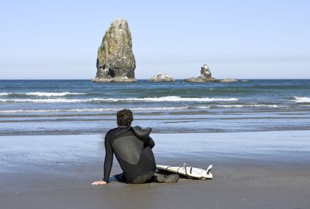 A surfer waiting for the right waves is scanning the ocean horizon while resting on a sandy beach. The seastack in the distance is just off Cannon Beach in Oregon.