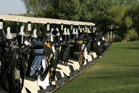 golf cart: A row of golf carts are lined up at the starting area and are ready to start the days round with a shotgun start tournament. The carts are loaded in the back with a variety of golf clubs and golf bags. Stock Photo