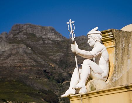 A statue of Hermes (or Mercury) holding his staff while watching over a courtyard from the roof of the Castle of Good Hope in Cape Town, South Africa.
