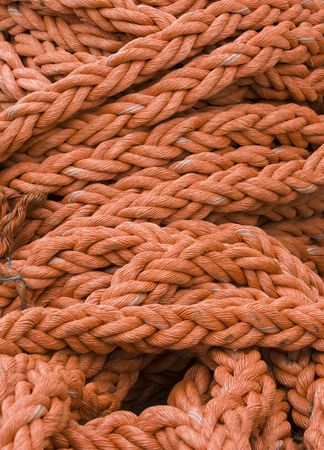 An orange rope all heaped together on a dock in the Victoria and Albert waterfront in Cape Town, South Africa. Lines like these are used to tie up ships at the pier. Stock Photo - 3659830