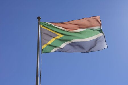 flagpoles: The flag of South Africa, flying in the wind over the Castle of Good Hope in Cape Town. The South African flag is the only one in the world to have six colors. Stock Photo