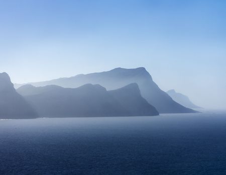 Sout Africa Coast. A mountain range, shrouded in mist, is silhouetted against the sky.