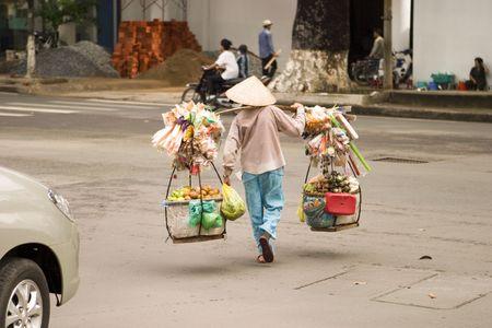 A Vietnamese street vendor in Ho Chi Minh City (Saigon) carrying their goods across a street. Imagens