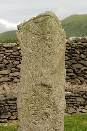 supposedly: An ancient Celtic tombstone in an old monastery with many of the old decorations still showing. The Cross at the top was supposedly added later.. This was the tallest stone still standing -- the other ruins were all no more than the foundations from the o Stock Photo