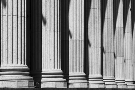 Post Office Columns. A row of stone columns provide a classical entrance to the New York City post office. In black and white.