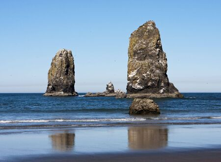 Two large sea stacks on Cannon Beach in Oregon State. These two weather-beaten rocks are located near Haystack Rock. photo