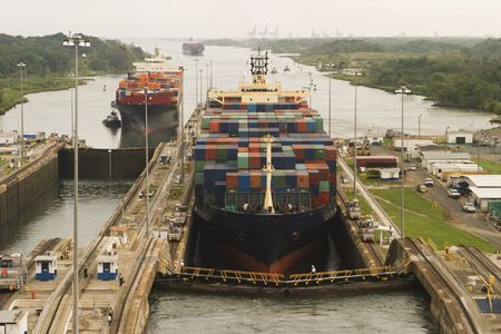 assisted: Two freighters, assisted by tugboats, are preparing to transit the Panama Canal starting at Gatun Locks on the Atlantic side. These container ships are fully loaded with cargo heading west towards the Pacific.