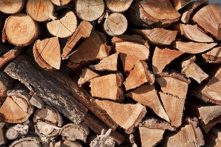 A stack of wood logs that have been split into firewood. Many of the logs show the growth rings as well as the tree bark.