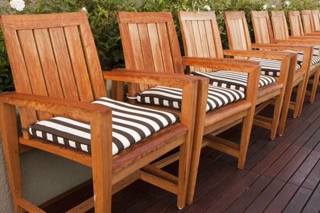 A line of teak wood chairs with black and white striped cushions arranged in a row on a deck at a luxury hotel. Imagens