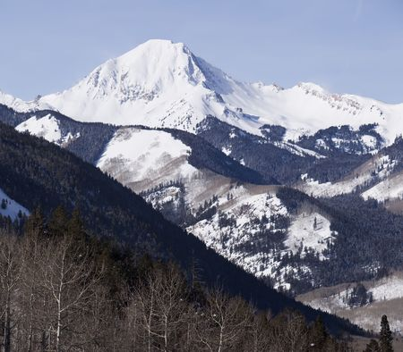 A view of Mt. Daly in the Elk mountain range in Colorado. A view of wilderness capped with a snow-covered peak.