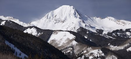 A panorama view of Mt. Daly in the Elk range in Colorado. The peak is centered on a long mountain ridge.
