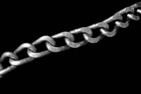 traction: The stell links of a tire chain stretched out diagonally across a tire. Isolated to a black background for contrast. Stock Photo