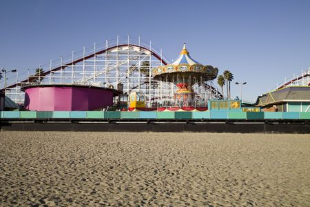 An old-fashioned amusement park with a beach boardwalk and an old wooden roller coaster.