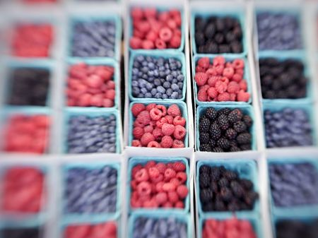 progressively: Baskets of raspberries, blueberries, blackberries and strawberries on display in a market. The colors contrast throughout the checkerboard-like pattern. Note that this image is sharp in the center but blurs progressively towards the edges