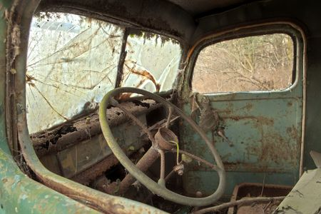 The interior of the drivers cab of an old, abandoned green truck that has been stripped down to the bare minmum. Stock Photo