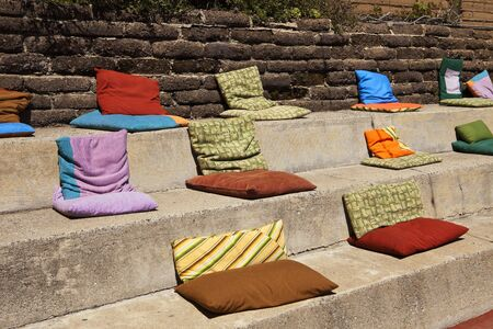 Soft, colorful cushy pillows on sun-drenched concrete steps form a informal and comfortable waiting area for a restaurant in California. Reklamní fotografie