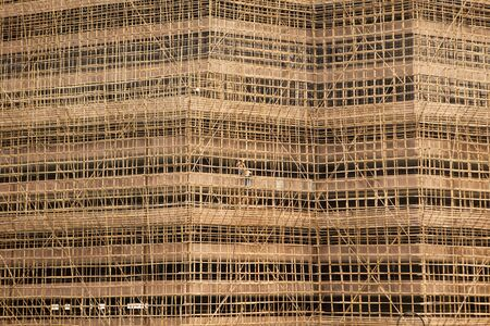 A building under construction in Hong Kong is framed with bambo scaffolding. Two men are visible in the center of the image, dwarfed by the size of the project. photo