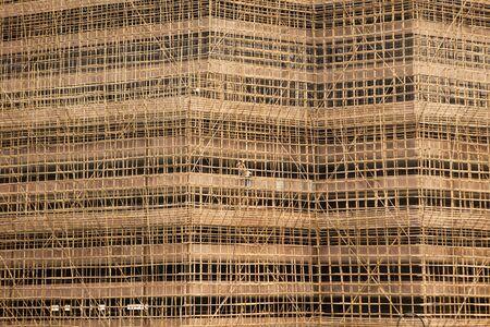 andamios: Un edificio en construcci�n en Hong Kong se enmarca con andamios bambo. Dos hombres son visibles en el centro de la imagen, dwarfed by el tama�o del proyecto. Foto de archivo