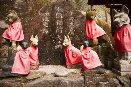 capes: Stone foxes (kitsune), dressed with red capes, act as guardians to Japanese Shinto shrines. The foxes also act as messengers to Inari, the goddess of agriculture. Stock Photo