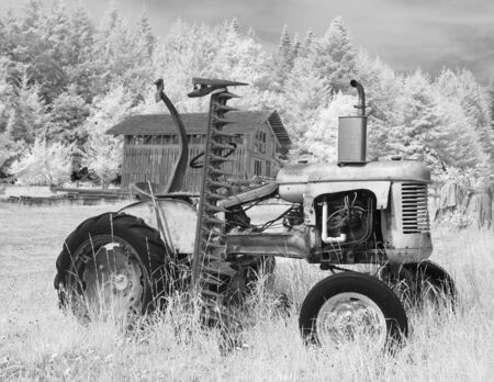 barn black and white: An old tractor on a farm with a barn in the background. In black and white infrared. Stock Photo